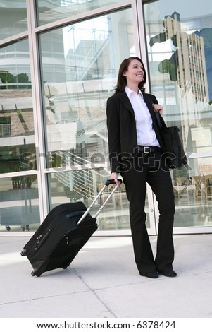 A pretty business woman traveling with a suitcase - stock photo