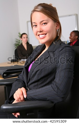 A pretty business woman with her team in the office