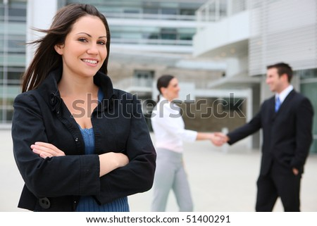 A pretty business woman with team handshake in background - stock photo