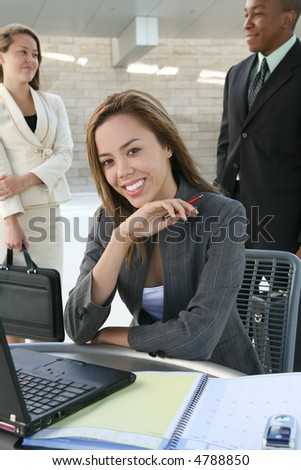 A pretty business woman working on her laptop computer - stock photo