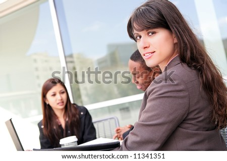 A pretty business woman working with co-workers in background - stock photo