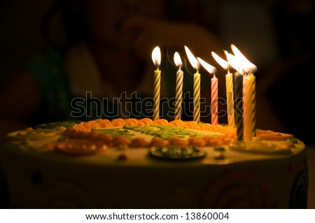 a pretty cake ready for the birthday person to blow out the candles. There are 10 candles on the cake. - stock photo