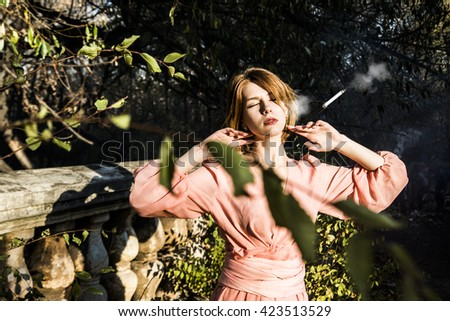 A pretty caucasian redhead girl dreaming with closed eyes. Sunny light and shadow on vintage retro concrete empire fence. bob hairstyle - ginger woman. Cigarette in mouthpiece with smoke - stock photo