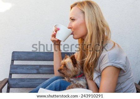 A pretty caucasian woman at home sitting on the porch and drinking coffee. She is resting. Outdoor photo. - stock photo