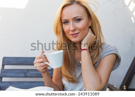 A pretty caucasian woman at home sitting on the porch and drinking coffee. She is resting. Outdoor photo.