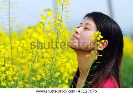 A pretty chinese women in rapeseed flowers. - stock photo