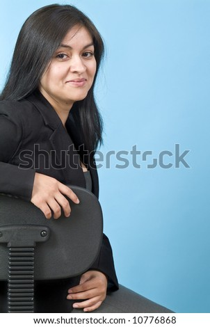 A pretty confident young woman sitting in an office chair, taken against a blue background. - stock photo