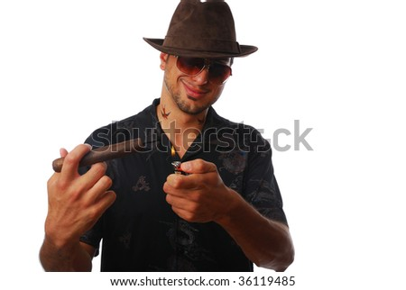 A pretty cool guy in a hat lighting a cigar - stock photo