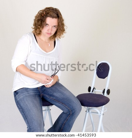 a pretty curly girl is cleaning her pair of glasses and waiting for her guest - studio photo