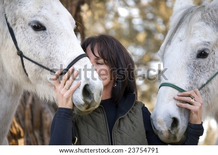 A pretty dark haired woman with two grey horses is kissing one of them on the muzzle. - stock photo