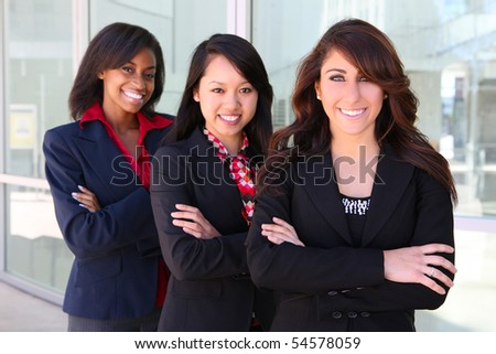 A pretty diverse young business woman team at office building - stock photo