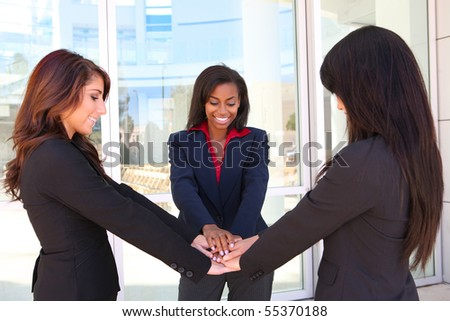A pretty diverse young business woman team at office building celebrating success - stock photo