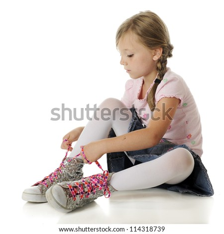 A pretty elementary girl tying heart-covered, neon pink laces on oversized sparkly high-top sneakers.  On a white background. - stock photo