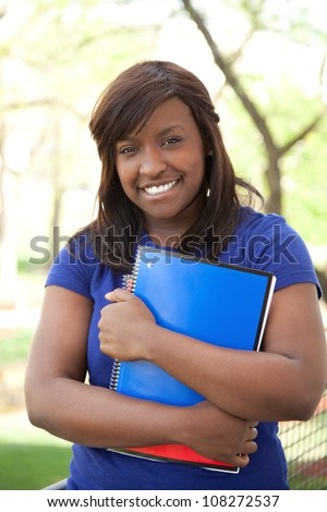 A pretty female African-American college or university student holding books, outdoors