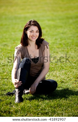 A pretty female isolated on a background of grass in a park