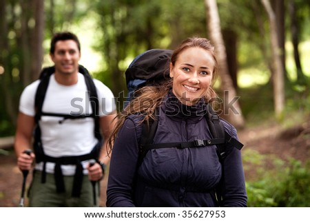 A pretty female on a camping trip with a male in the background - stock photo