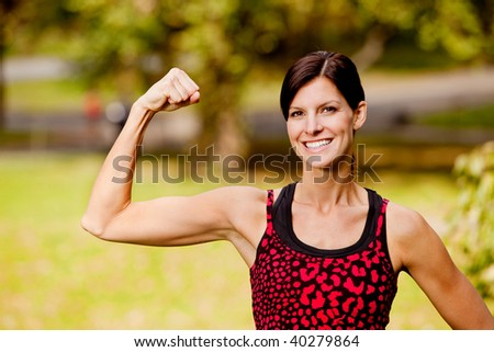 A pretty fitness model flexing her bicep - stock photo