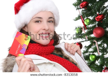A pretty girl at Christmas holding a gift card - stock photo