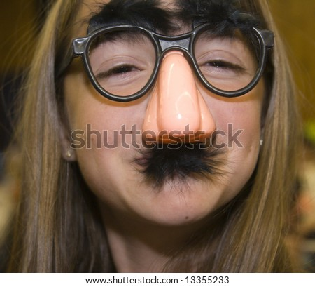 A pretty girl disguised with fake glasses, nose, and mustache