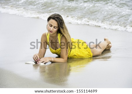 A pretty girl, dressing in a bright yellow address, barefoot and whole body wet, is lying on the beach, playing with seashell, into deeply thinking / Daydream on the beach - stock photo