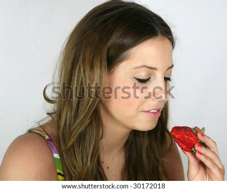 A pretty girl eats a strawberry for her lunch
