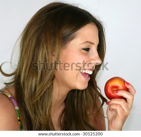 A pretty girl eats an apple for her lunch - stock photo