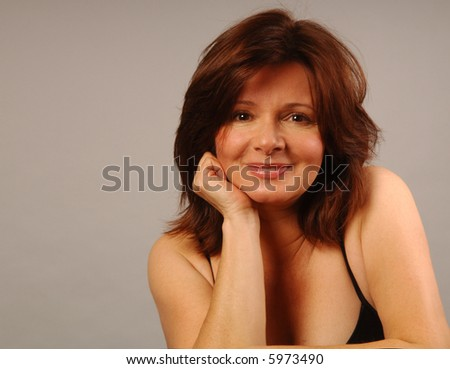 A pretty girl in a contemplative but smiling pose - stock photo