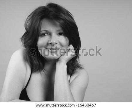 A pretty girl in a contemplative, smiling pose - stock photo