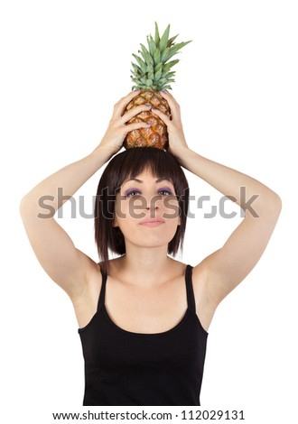 A pretty girl looking at camera while holding a pineapple on top of his head. Isolated on white. - stock photo