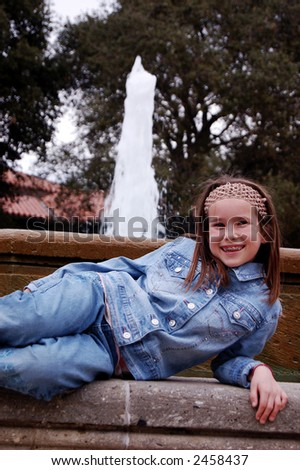 A pretty girl lying down in front of a fountain. - stock photo