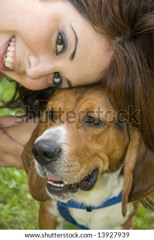 A pretty girl posing with her beagle dog.