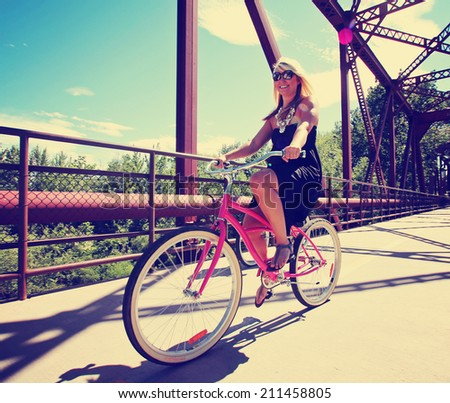 a pretty girl riding a bicycle across a bridge toned with a retro vintage instagram like filter  - stock photo