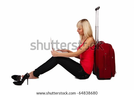 A pretty girl sitting on  a floor with the laptop on her knees - stock photo