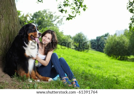 A pretty girl with a dog in the park - stock photo
