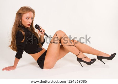 A pretty girl with a microphone singing. Closeup on a white background. - stock photo