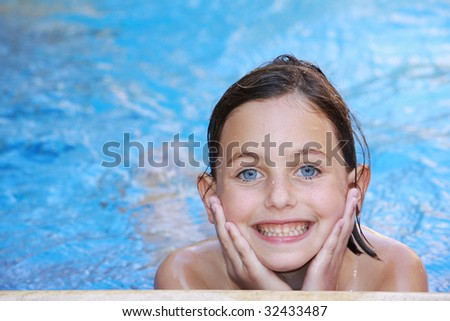 a pretty girl with blue eyes swimming in a swimming pool - stock photo
