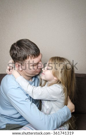 A pretty girl with her father on the sofa smiling and hugging after quarrel