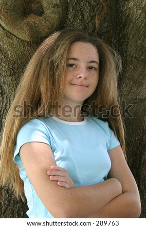 A pretty girl with long hair posing against a tree.