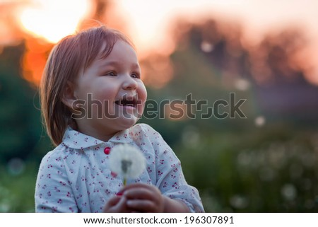 A pretty happy little girl with a dandelion in the field - stock photo