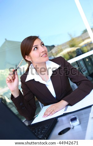 A Pretty Hispanic Business Woman at office on laptop computer - stock photo