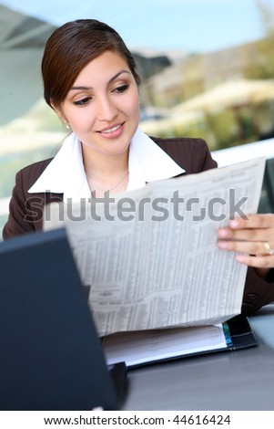 A Pretty Hispanic Business Woman with laptop computer reading newspaper - stock photo