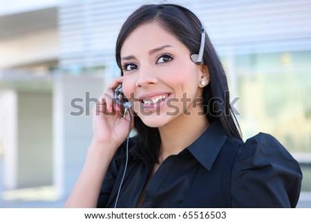 A pretty hispanic customer service business woman on the phone - stock photo