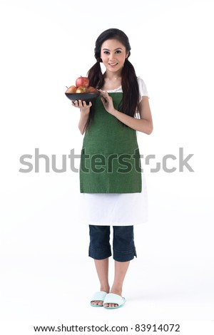A pretty housewife holding a bowl of apples - stock photo