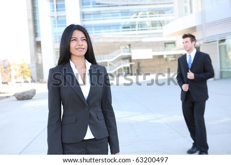 A pretty Indian business woman at the office with man worker in background - stock photo