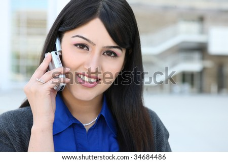 A pretty Indian business woman on the phone at office building - stock photo