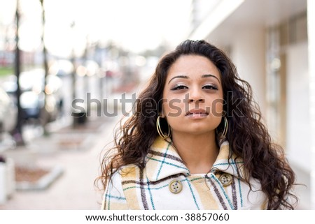 A pretty Indian woman with curly brown hair posing outdoors. - stock photo