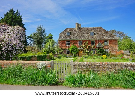 A pretty individual red brick with slate roof Cotswold country cottage in the heart of the Cotswolds, Gloucestershire, United Kingdom - stock photo