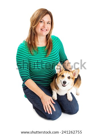 A pretty lady wearing a green and blue striped shirt sitting and holding a Pembroke Welsh Corgi dog - stock photo