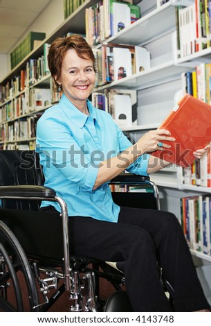 A pretty librarian in her wheelchair shelving books. - stock photo