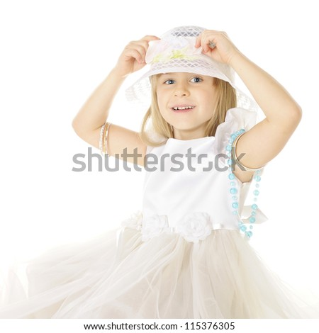 A pretty little girl, dressed mostly in white.  She's happily adjusting the pastel bow on her hat.  On a white background.